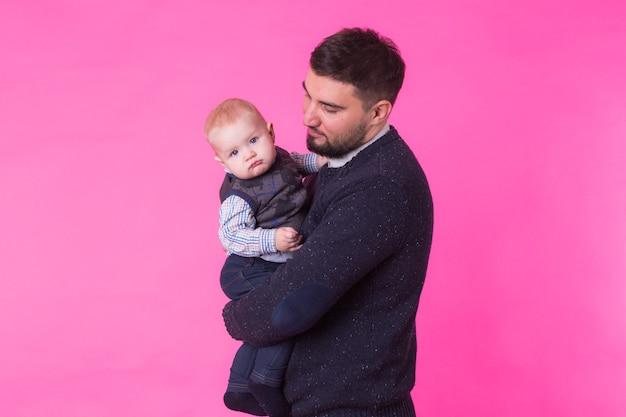 Padre felice con un figlio bambino isolato su rosa.