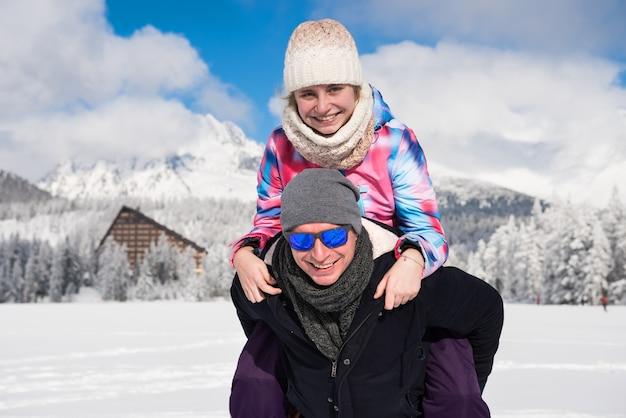 Padre felice con la figlia che gode delle vacanze invernali sulle montagne