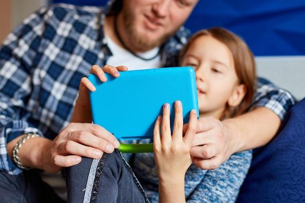 Padre felice con la figlia utilizzando computer tablet in soggiorno, al divano di casa