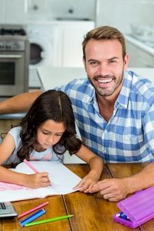 Padre felice con la figlia che scrive in libro a casa