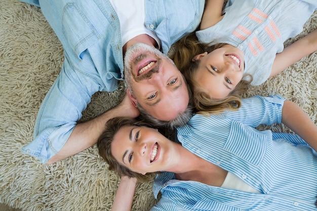 Padre felice con suo figlio e sua figlia sdraiati sul tappeto