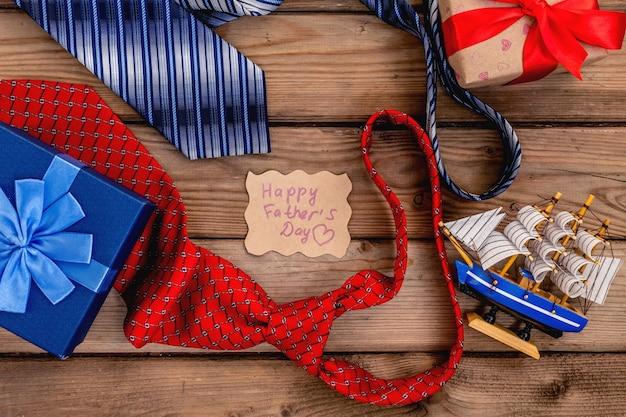 Scatole regalo per la festa del papà felice con cravatte rosse e blu su uno sfondo di legno rustico. scheda vista dall'alto.