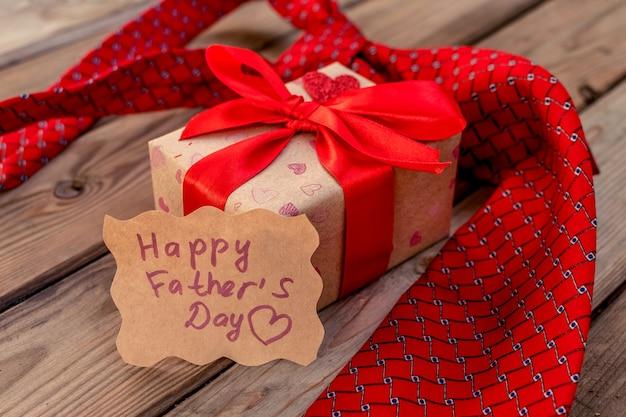Scatola regalo per la festa del papà felice con cravatta rossa su uno sfondo di legno rustico. biglietto d'auguri