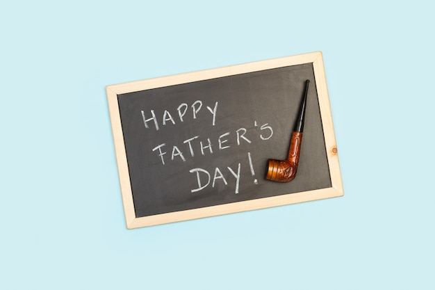 Il saluto di giorno di padri felice scrive con il gesso su una lavagna con un tubo