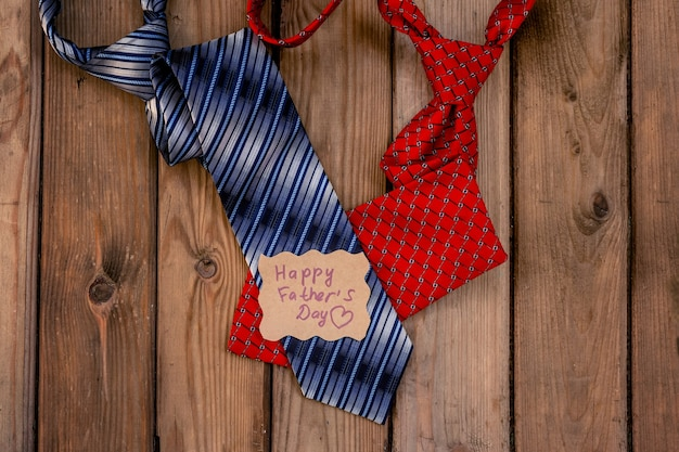 Happy fathers day cravatte rosse e blu su uno sfondo di legno rustico. nota artigianale con saluti.