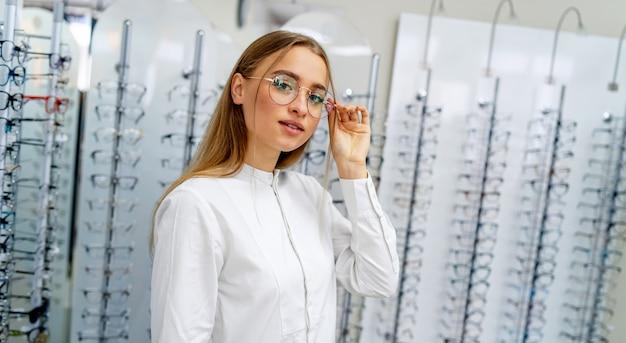 Felice cliente femminile o ottico è in piedi con il grezzo di occhiali nel negozio di ottica.