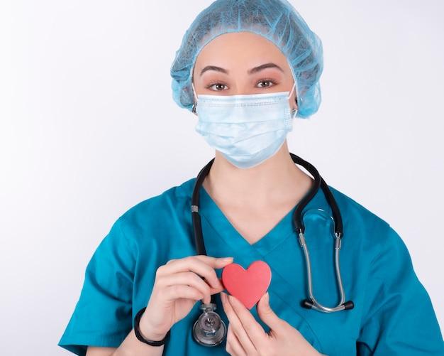 Felice dottoressa con cuore rosso, sul muro bianco, cuore rosso,