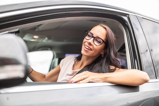 Felice autista donna con gli occhiali guarda attraverso il finestrino laterale aperto di un'auto che guida..