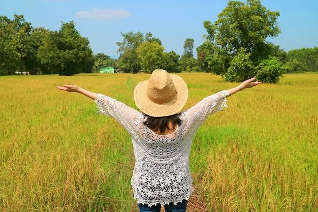 Felice agricoltore femminile alzando le braccia nelle risaie pronte per la raccolta