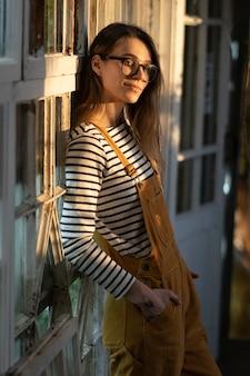 Fiorista femminile felice che posa alla vecchia parete della serra rilassata