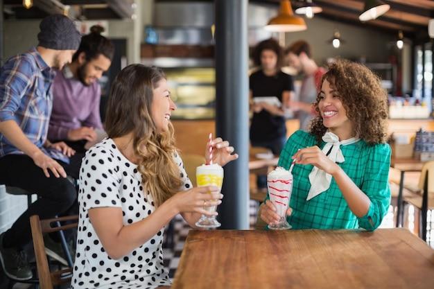 Amici femminili felici che esaminano mentre tengono i frullati
