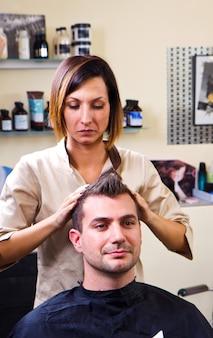 Felice parrucchiere femminile che sistema i capelli del cliente