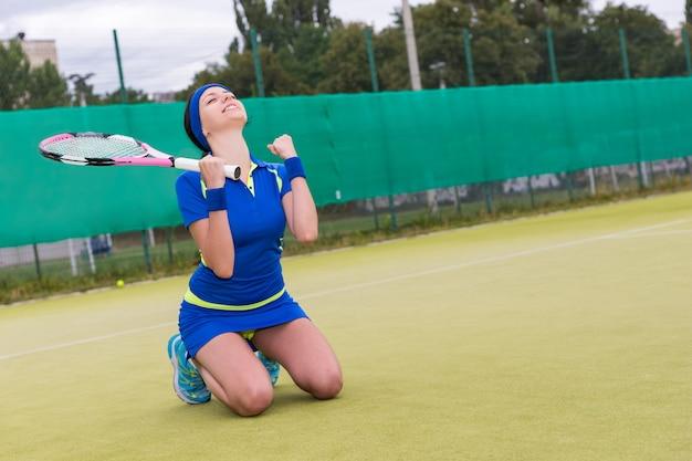 Felice giocatrice cadde in ginocchio e fece un pugno a causa della vittoria nella partita di tennis al campo da tennis in estate o in primavera