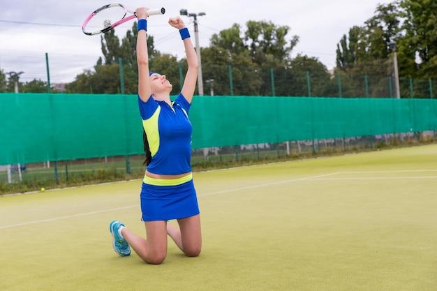 Felice giocatrice cadde in ginocchio e alzò le mani a causa della vittoria in una partita sul campo da tennis in erba verde in estate o in primavera