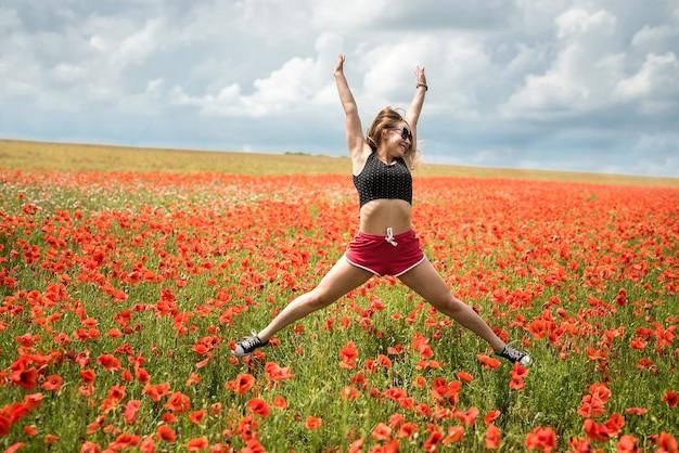 Felice femmina in abiti sportivi che salta nel campo di papaveri in una calda giornata estiva