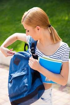 Studentessa felice chiudendo il suo zaino all'aperto