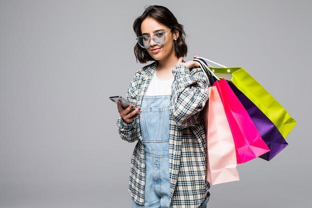Felice femmina con sacchetti di carta colorata che fa shopping, parla al cellulare, tiene in mano uno smartphone, fa una chiamata, sorride sognante. isolato su muro grigio, copia spazio