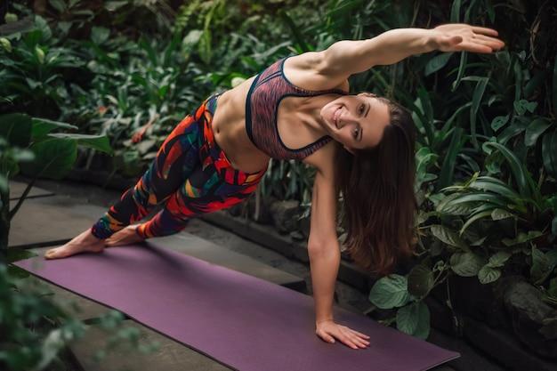 Istruttore femminile felice di yoga che allunga su una stuoia alla serra
