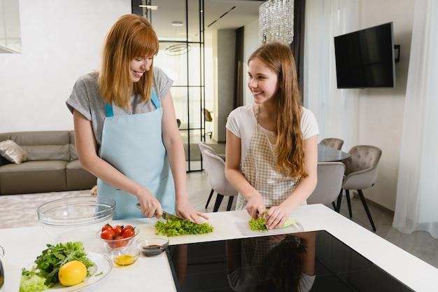 Femmine felici che indossano grembiuli, tengono in mano i coltelli e preparano insalata verde fresca con pomodori, succo di limone, rucola, olio d'oliva e salsa scura al chiuso