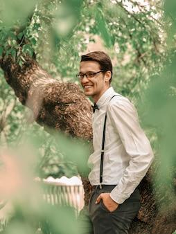 Fidanzato felice in piedi tra gli alberi nel giardino primaverile. il concetto di felicità