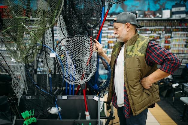 Felice pescatore che sceglie rete nel negozio di pesca, ganci e palline