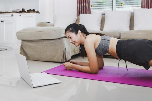 Esercizio asiatico di forma fisica di addestramento della donna di misura felice online con il computer portatile a casa