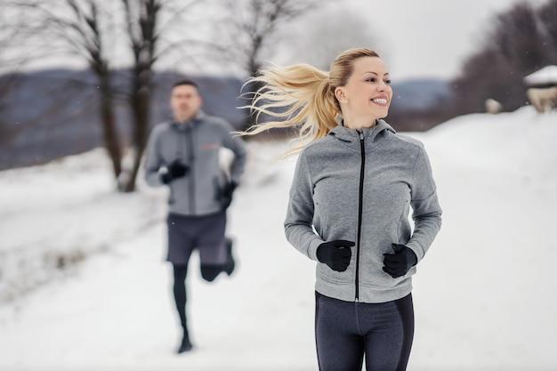 Sportiva felice in forma che corre la sua amica in natura al giorno di inverno nevoso. fitness insieme, fitness all'aperto, fitness invernale