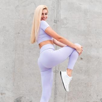 Felice modella di fitness donna bionda con un sorriso carino e un bel corpo che fa il riscaldamento prima di fare jogging per strada