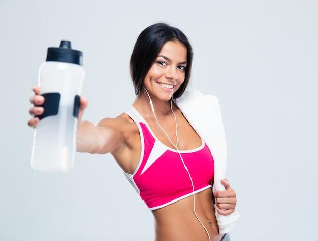 Felice donna fitness tenendo la bottiglia con acqua