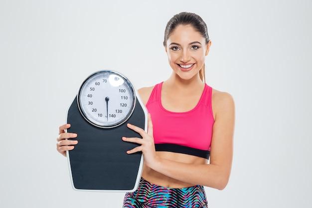 Felice fitness donna che tiene in mano una bilancia e guarda la telecamera