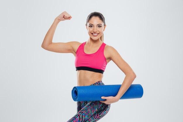 Donna felice di forma fisica che tiene stuoia di yoga e mostra i suoi bicipiti