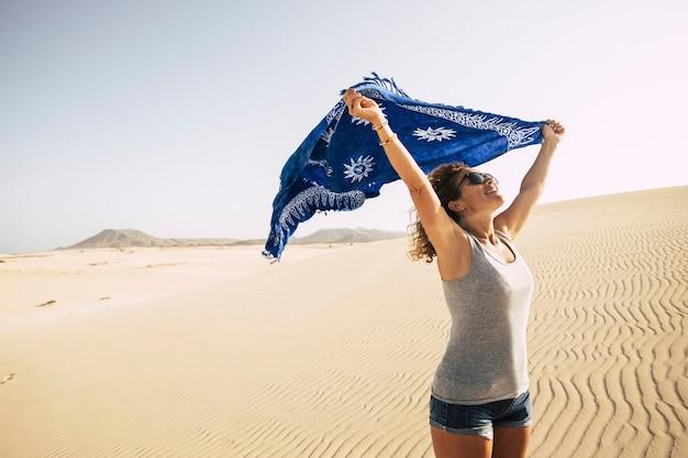 Bella signora felice e libera che si gode il vento nel deserto sabbioso
