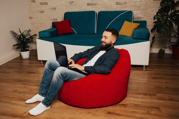 Uomo libero professionista felice che lavora al computer portatile che si siede sulla poltrona rossa a casa.
