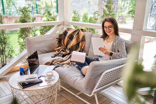 Libero professionista felice che lavora a casa con tablet.