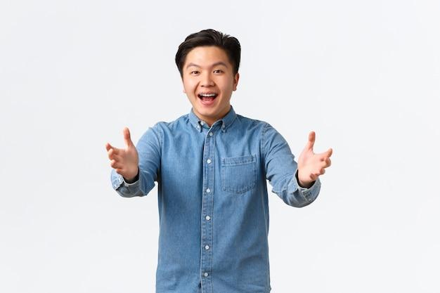 Felice studente maschio asiatico dall'aspetto amichevole che si congratula con l'amico, allungando le mani in avanti per l'abbraccio, dicendo congratulazioni, lodando peson con un ottimo lavoro, in piedi sfondo bianco eccitato.