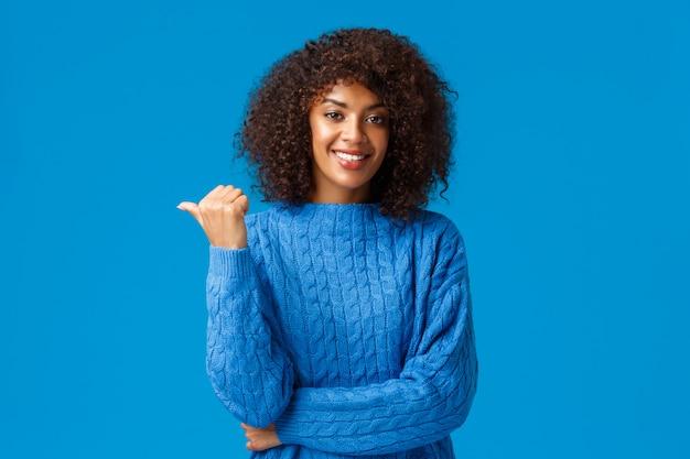 Felice amichevole socievole, afro-americana femminile in maglione invernale, condivisione link, consigli, puntando il pollice a sinistra per il tuo annuncio di check-out, sorridente in piedi blu