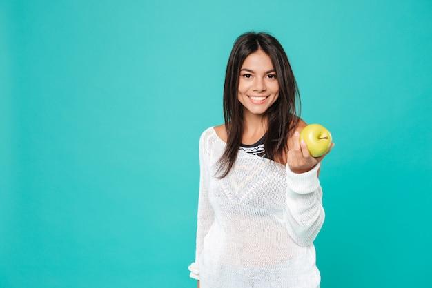 Giovane donna amichevole felice che sta e che vi dà mela fresca