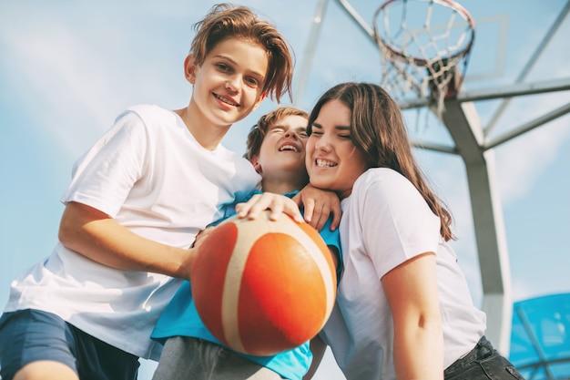 Amici felici stanno abbracciando in piedi sul campo da basket e si divertono. giochi sportivi