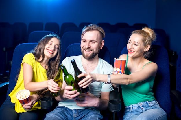 Amici felici che tintinnano bottiglie seduti al cinema