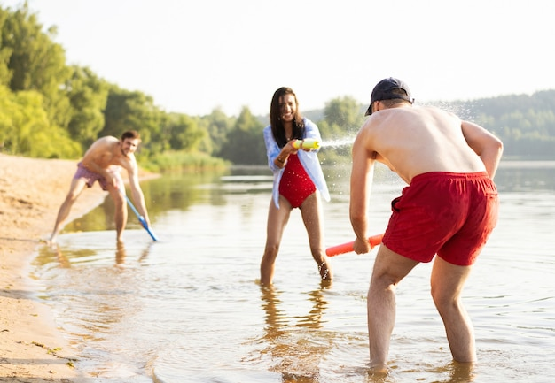 Amici felici che combattono con pistole ad acqua - gioventù, stile di vita estivo e concetto di vacanza