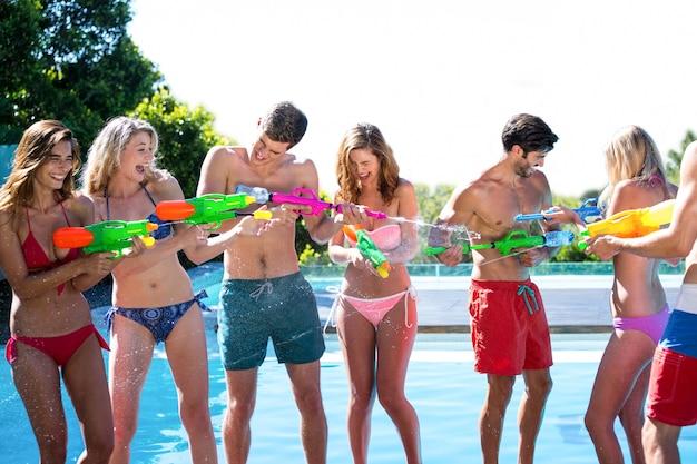 Amici felici che fanno battaglia con pistola ad acqua