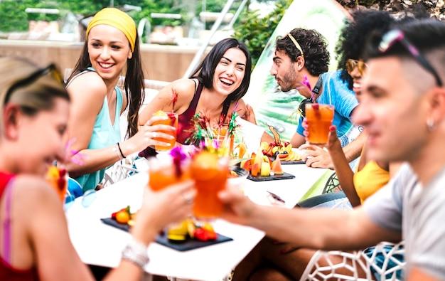 Amici felici che bevono cocktail alla festa in piscina