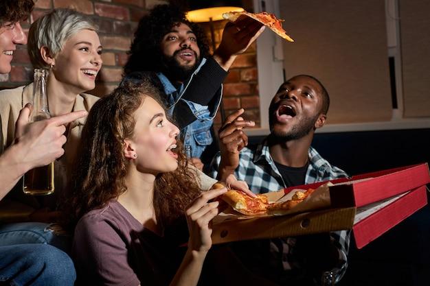 Amici felici che mangiano pizza e guardano film o serie tv a casa, gli studenti americani si godono il tempo libero dopo le lezioni, riposandosi dopo una dura settimana