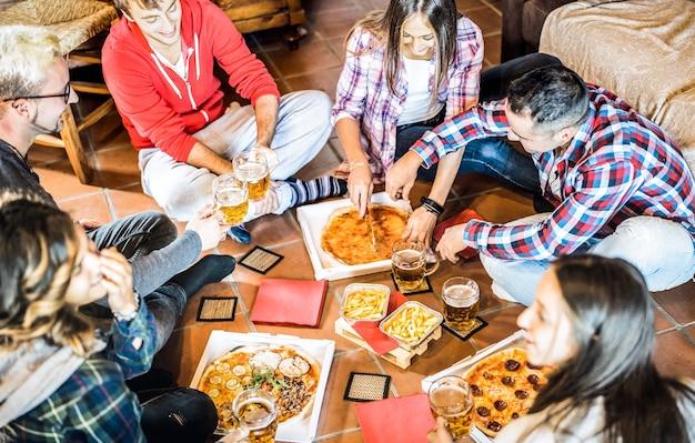 Amici felici che mangiano pizza da asporto a casa dopo il lavoro