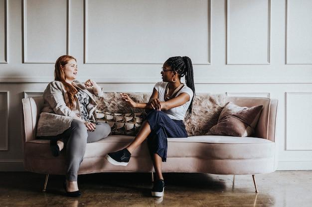 Amici felici che si godono una conversazione insieme sul divano
