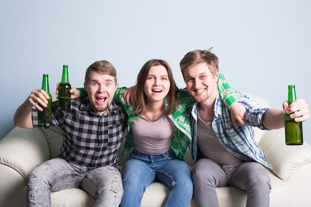 Amici felici o appassionati di calcio guardando il calcio in tv e celebrando la vittoria a casa.concetto di amicizia, sport e intrattenimento.