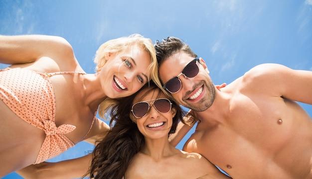 Amici felici che hanno divertimento sulla spiaggia