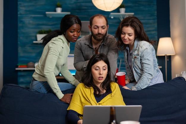 Amici felici che si divertono a bere birra parlando in videochiamata utilizzando il laptop. gruppo di persone multirazziali che trascorrono del tempo insieme seduti sul divano a tarda notte in soggiorno.