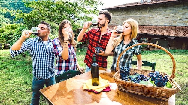 Amici felici che si divertono a bere al vigneto della cantina - concetto di amicizia con i giovani che si godono il raccolto insieme in fattoria - degustazione di vino rosso all'esperienza indie all'aperto - filtro retrò vintage