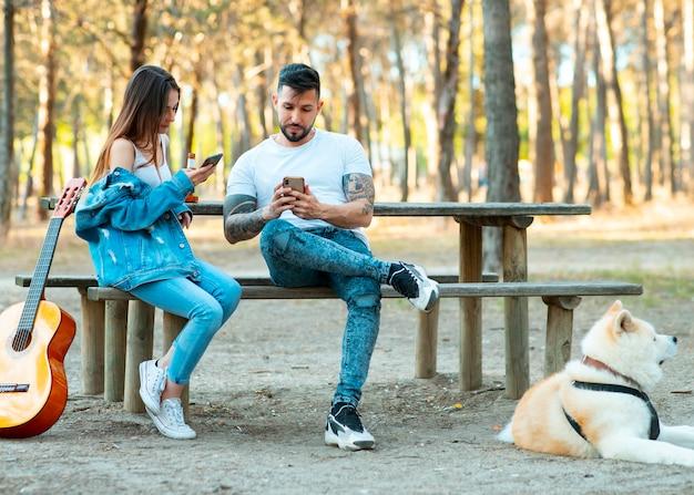 Amici felici che si divertono all'aperto pic-nic, giovani incoraggiano l'uso dello smartphone, weekend estivo serale - amicizia